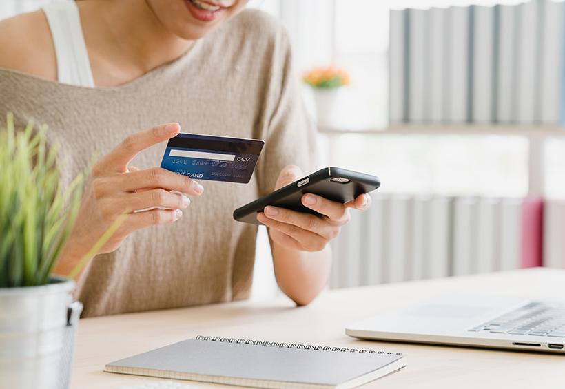 Mujer con tarjeta de crédito y celular
